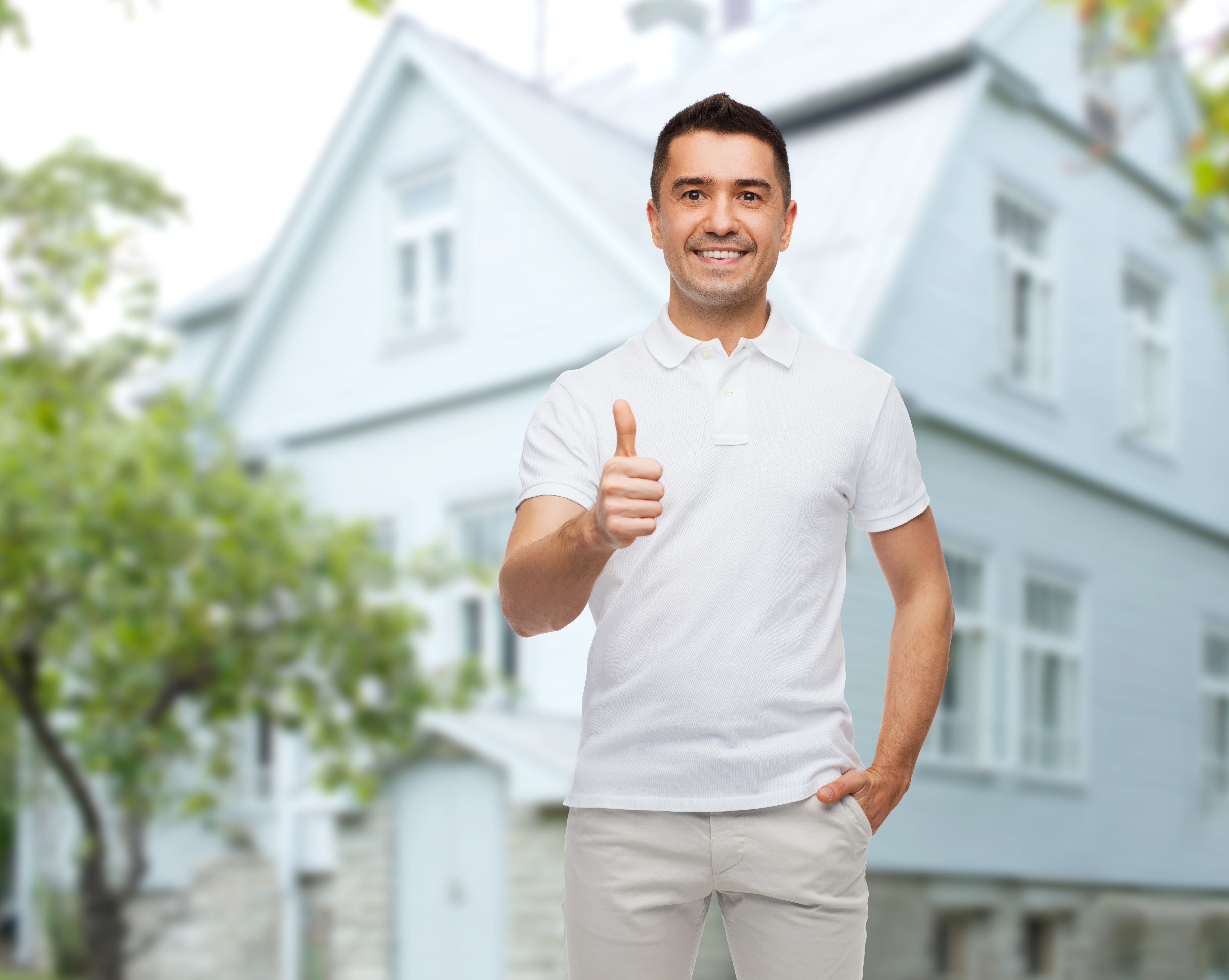 man showing thumbs up over house background